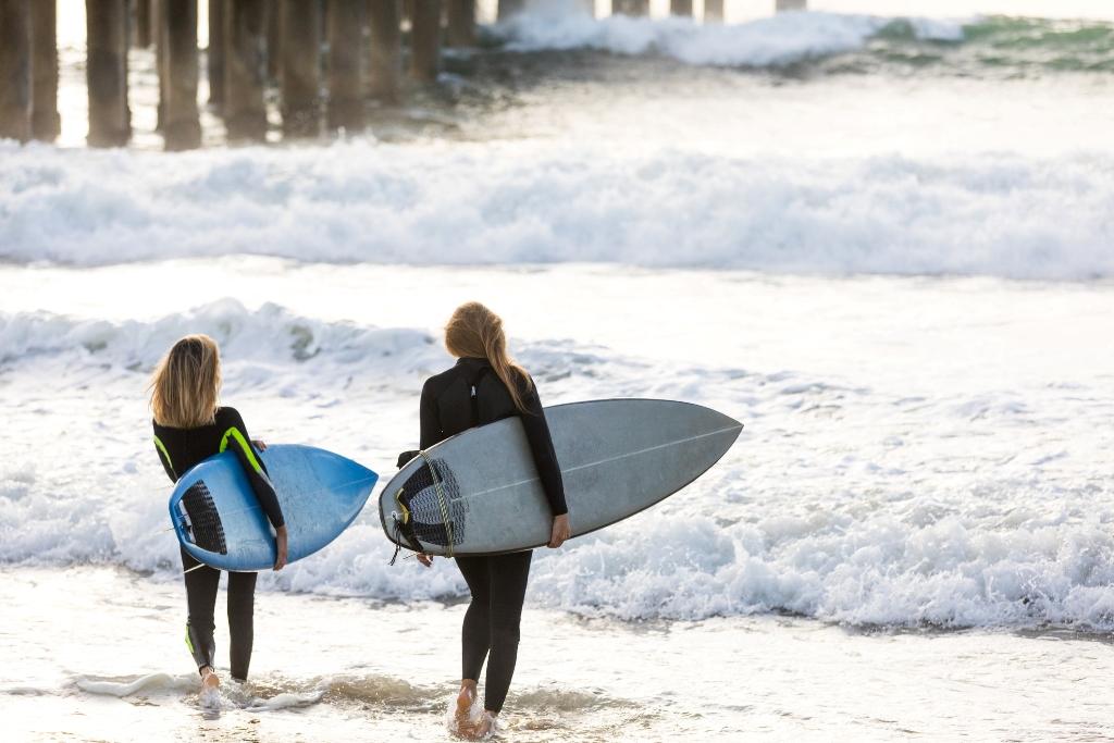 Two girls preparing to sufr in Manhattan Beach